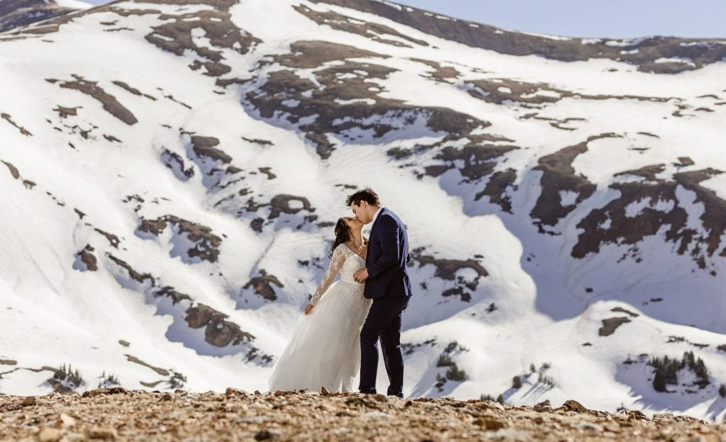 a couple eloping in winter between the snowy mountains of Colorado